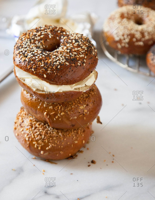Stack of bagels with one filled with cream cheese