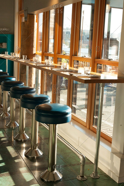 Wooden bar by a window with blue stools