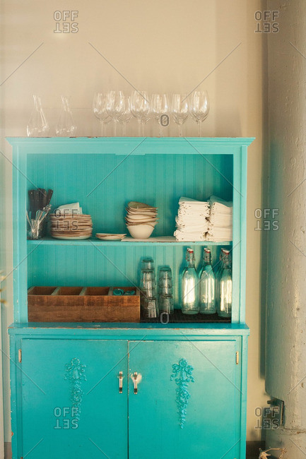 Blue cabinet with glassware, napkins and silverware