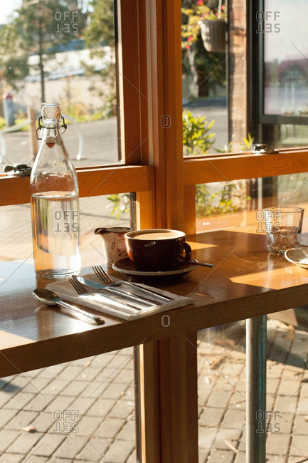 Coffee and water on a restaurant table by a window