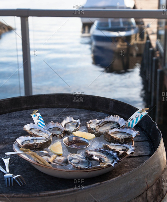 Oysters on ice with mignonette sauce served on a barrel