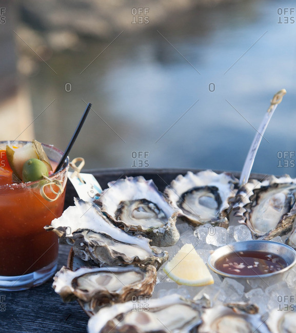 Oysters on ice with mignonette sauce served with a cocktail
