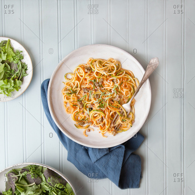 Spiralized zucchini noodles dish served with salad