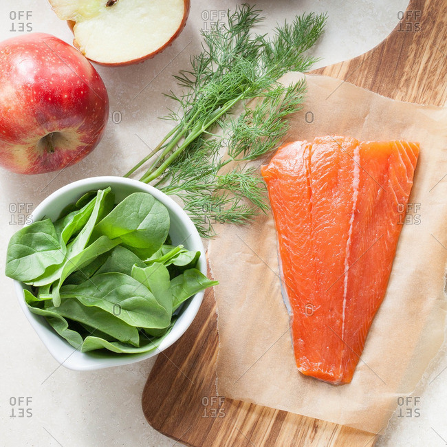 Raw fish fillet on a cutting board by a bowl of spinach, dill and apples