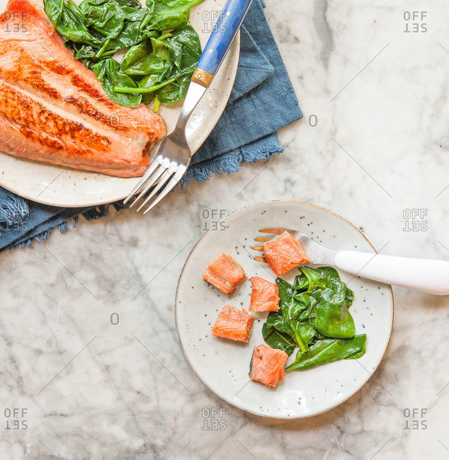 Grilled fish fillet served with cooked spinach