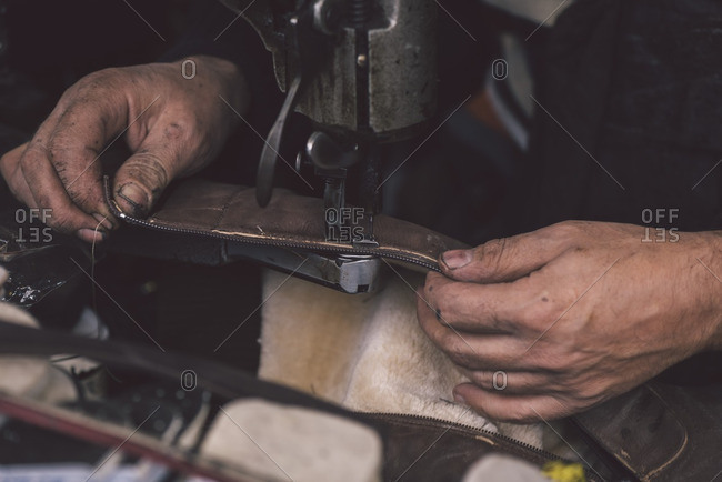 A shoemaker sewing a piece of leather