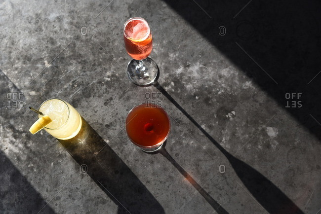 Cocktails on surface with shadows from sunlight