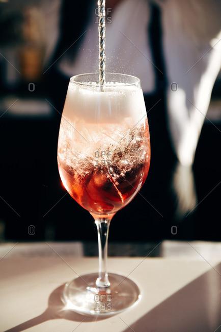 Bartender stirring a fizzy cocktail