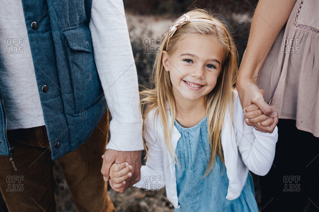 Close up of a little girl holding mom and dads hands