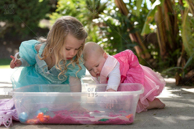 Two young children playing in box of pink sand