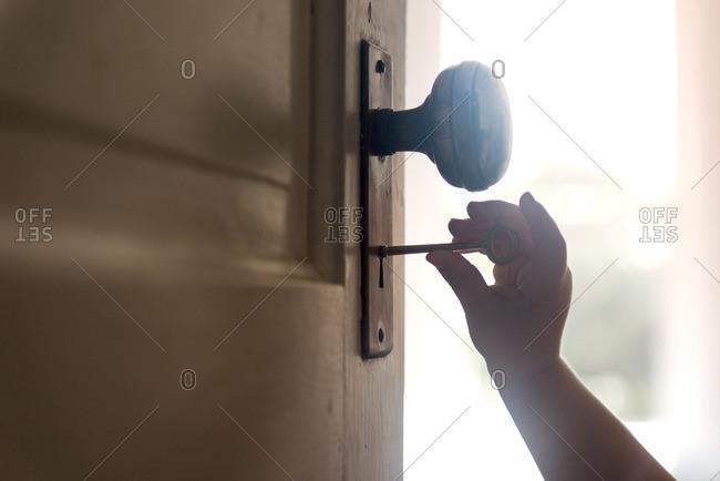Child's hand unlocking door with vintage key