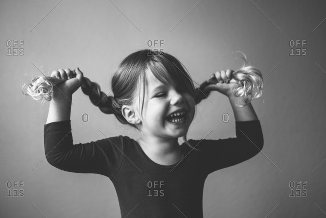 Laughing toddler girl pulling out her braids
