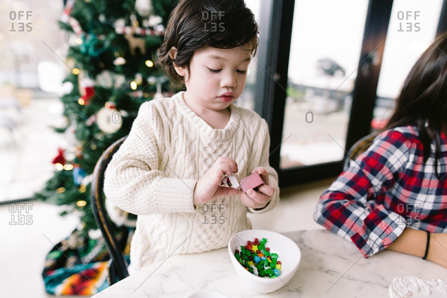 Little boy holding candy to decorate a gingerbread house