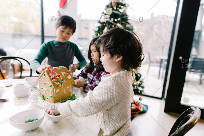 Three siblings using candy to decorate a gingerbread house