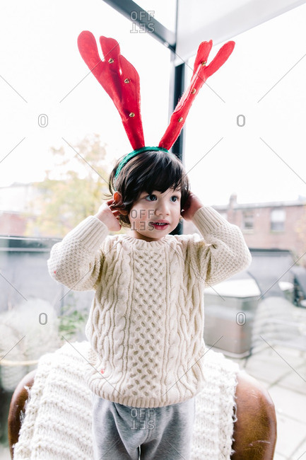 Boy in a sweater wearing red and green reindeer antlers