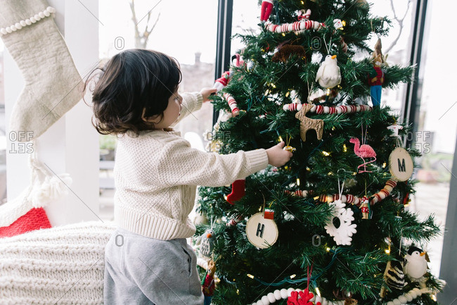 Little boy helping decorate a Christmas tree