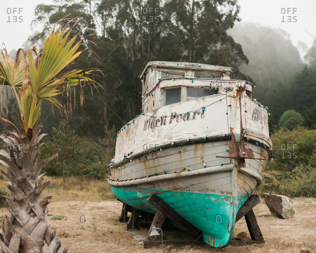 California, USA - September 25, 2012: Weathered dry docked boat decorated with lights