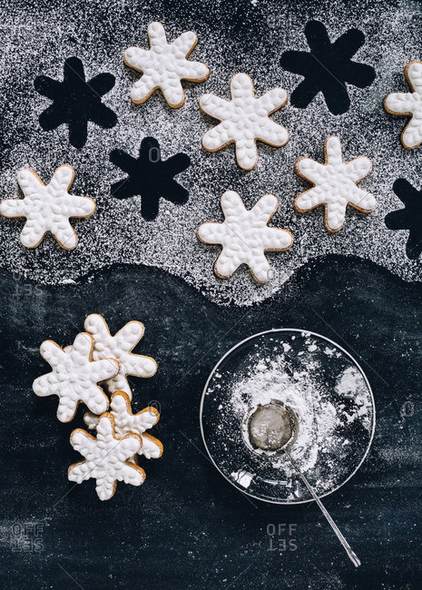 Iced snowflake cookies and a bowl of confectioner's sugar