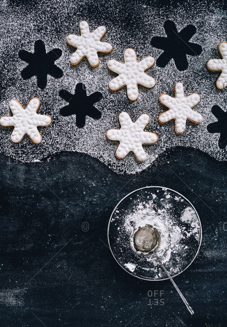 Frosted snowflake cookies and a bowl of powdered sugar