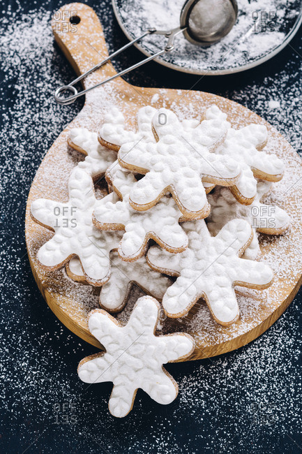 Iced snowflake cookies on a round wooden slab dusted with sugar