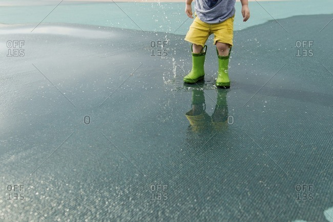 Low section of boy in rubber boots splashing water on wet road