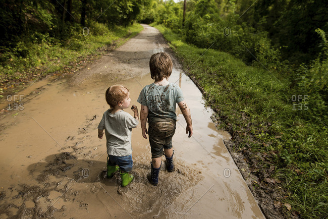 Rear view of messy brothers walking in dirty puddle on road