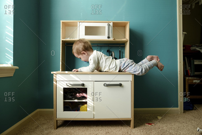 Boy lying on wooden cabinet at home