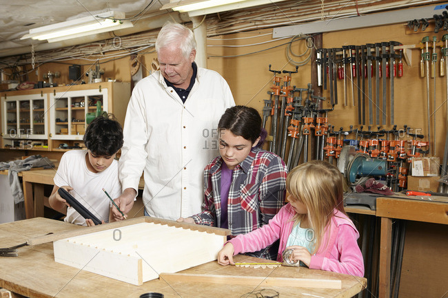 Carpenter teaching students in workshop