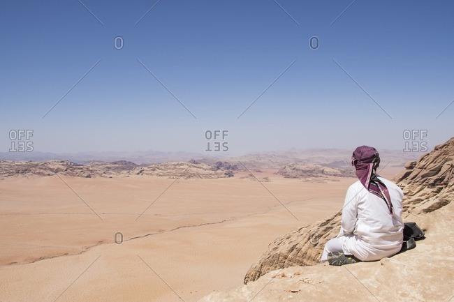 Rear view of man sitting on rock and looking at view