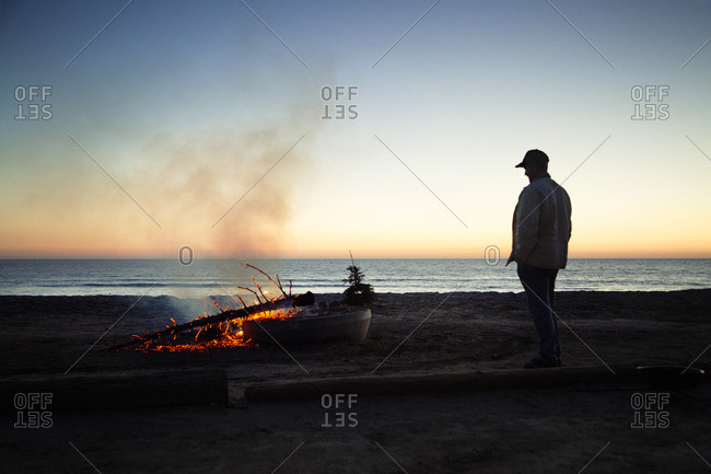 Man looking at burning wood at beach against clear sky