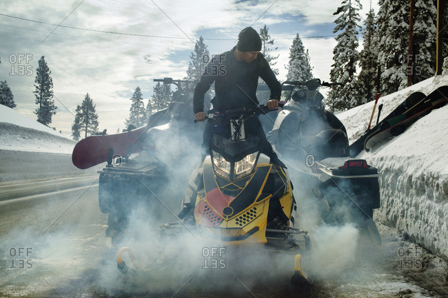 Man snowmobiling on road