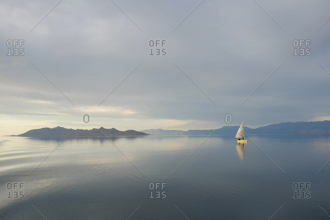 Scenic view of sailboat in lake against cloudy sky