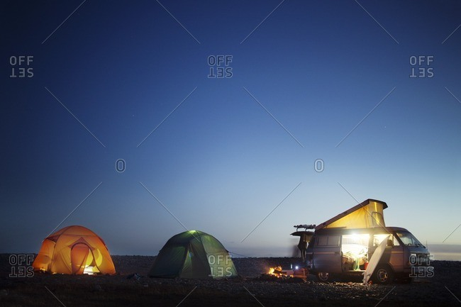 Camping equipment at beach against clear blue sky