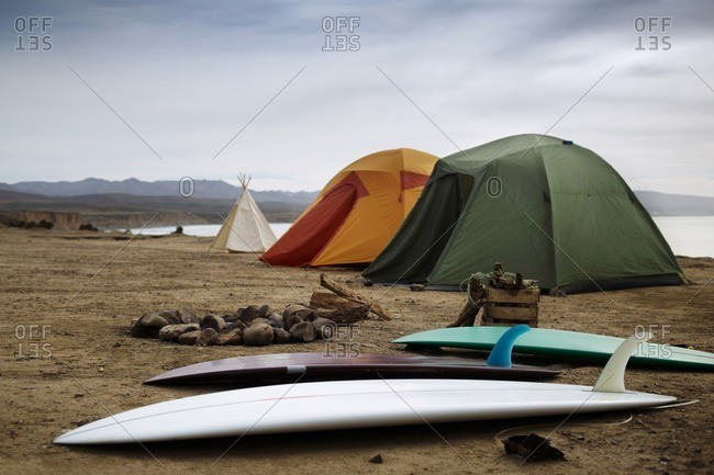 Camping equipment at beach against clear sky