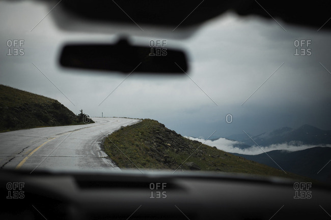 Country road by clouds covered mountains seen through car windshield