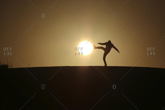 Optical illusion of silhouette man kicking sun during sunset