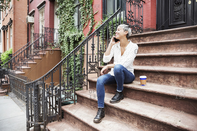 Happy woman talking on mobile phone while sitting on steps with coffee cup