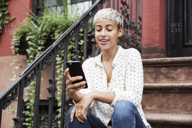 Happy woman using mobile phone while sitting on steps