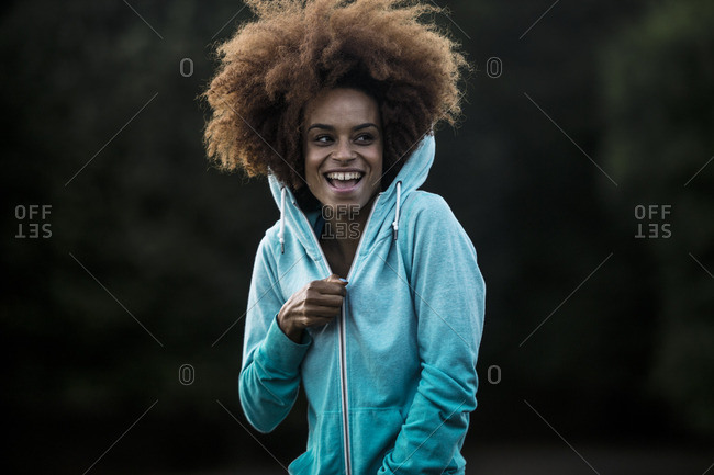 Cheerful woman wearing hooded shirt in park