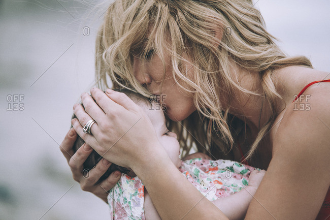 Woman with blond hair kissing daughter