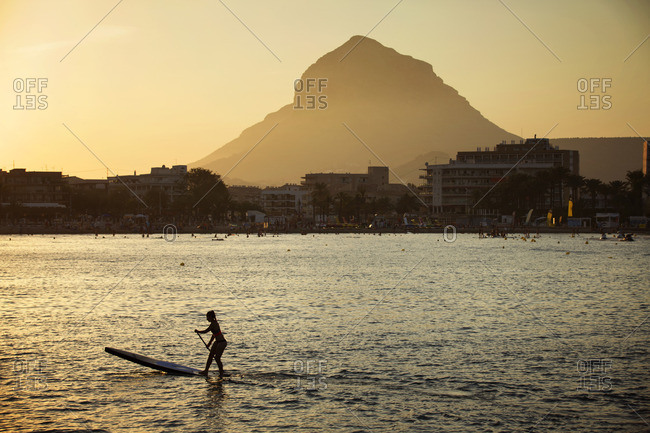 Athlete paddle boarding in sea against sky