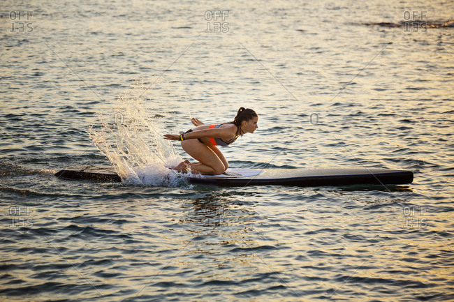 Woman kneeling on paddleboard while splashing water in sea