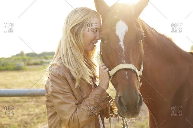 Happy woman stroking horse in farm