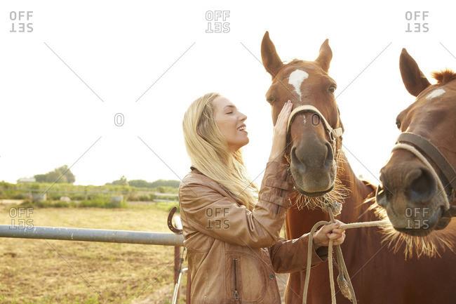Farmer stroking horse in farm against clear sky