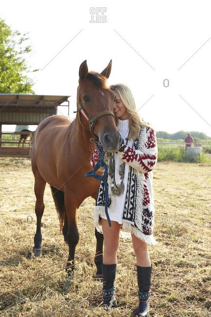 Rancher stroking horse on farm against clear sky