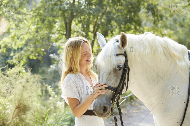 Happy woman stroking white horse in farm