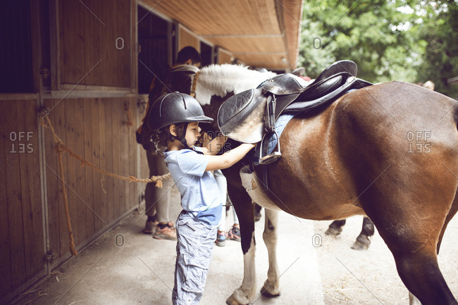 Boy with horse at stable