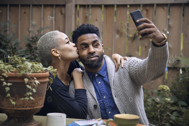 Woman kissing boyfriend while taking selfie in backyard