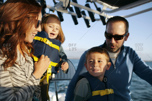 Children traveling with parents in sailboat on sunny day