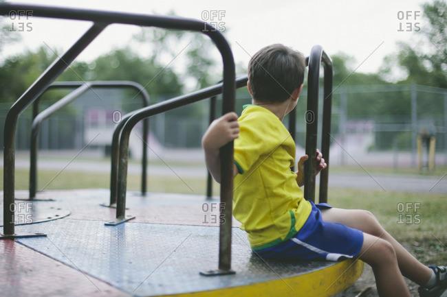 Boy sitting on Merry-Go-Round in playground